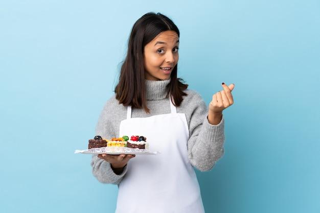 Ciasto szef kuchni trzyma dużego tort nad błękit ścianą robi pieniądze gestowi