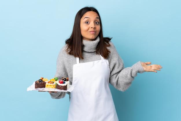 Ciasto szef kuchni trzyma dużego tort nad odosobnioną błękit przestrzenią robi wątpliwość gestowi