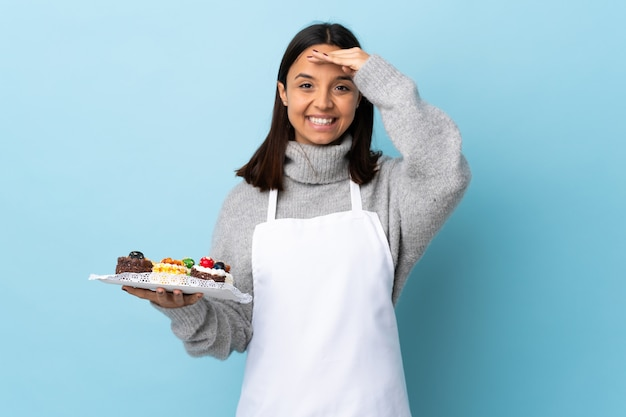 Ciasto szef kuchni trzyma dużego tort nad odosobnioną błękit ścianą salutuje ręką z szczęśliwym wyrażeniem