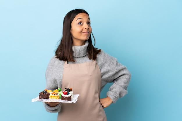 Ciasto szef kuchni trzyma dużego tort nad odosobnionym błękitem i przygląda up.