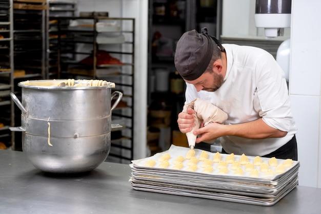 Ciasto szef kuchni z ciastkową torby gniosącą śmietanką przy ciasto sklepem.