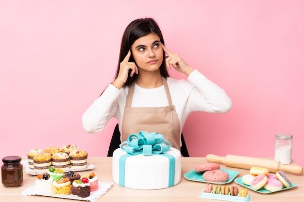 Ciasto szef kuchni z dużym tortem w stole nad odosobnioną menchii ścianą ma wątpliwości i główkowanie