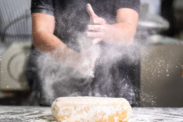 Ciasto szefa kuchni klascze jego ręki z mąką podczas gdy robić ciastu