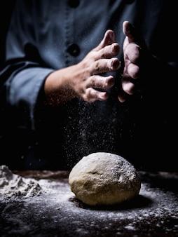 Ciasto szefa kuchni ręka kropi białą mąkę nad surowym ciastem na kuchennym stole.