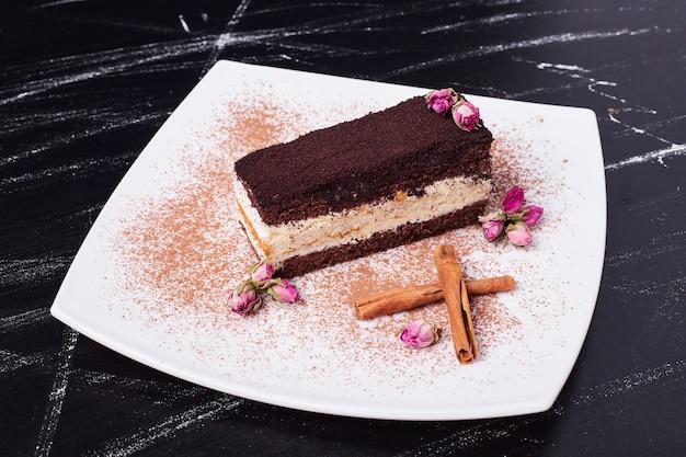Ciasto tiramisu udekorowane suszonymi kwiatami i cynamonem na białym talerzu.