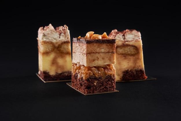 Ciasto tiramisu z trzema warstwami biszkoptu czekoladowego i naturalnego syropu kawowego z koniakiem i śmietaną. trzy kwadratowe kawałki w rzędzie ozdobione bitą śmietaną i kakao, odizolowane na czarnej ścianie.