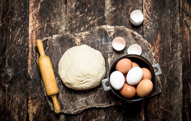 Ciasto tło. ciasto z wałkiem i świeżymi jajkami na starej drewnianej desce na rustykalnym stole.