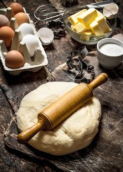 Ciasto tło. świeże ciasto z różnymi składnikami na drewnianym stole.