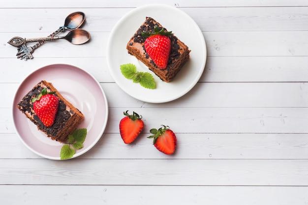 Ciasto truflowe z czekoladą, truskawkami i miętą na białym drewnianym stole. selektywne ustawianie ostrości. skopiuj miejsce
