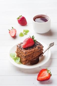 Ciasto truflowe z czekoladą, truskawkami i miętą na białym drewnianym stole. selektywne ustawianie ostrości.