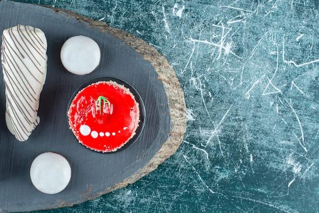 Ciasto truskawkowe i różne słodycze na kawałku drewna.
