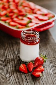 Ciasto truskawkowe krem i domowej roboty jogurt z truskawkami i dżemem na starym drewnianym stole