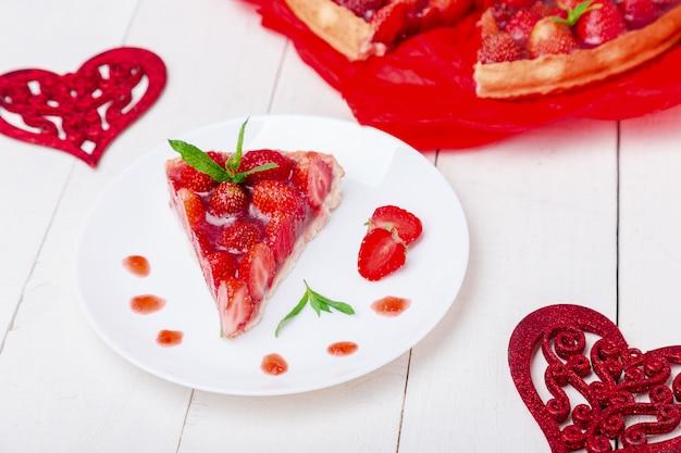 Ciasto truskawkowe na białym talerzu i białym drewnianym stole,