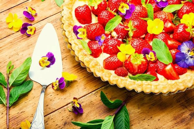 Ciasto truskawkowe ozdobione listkami i kwiatami mięty.tradycyjne ciasto truskawkowe lub tarta
