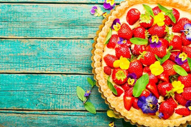 Ciasto truskawkowe ozdobione listkami i kwiatami mięty