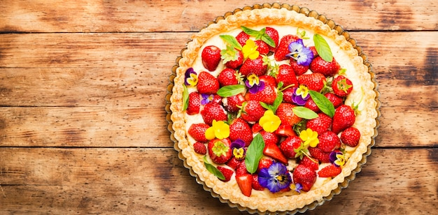 Ciasto truskawkowe ozdobione listkami mięty i kwiatami. skopiuj miejsce,