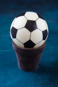 Ciasto w formie czarno-białej kulki w czekoladowym garnku na stole jako prezent dla łasucha i fana europejskiej piłki nożnej
