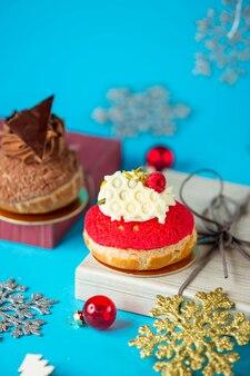 Ciasto w kształcie pączków z czerwonym blatem ozdobionym kremem i malinami