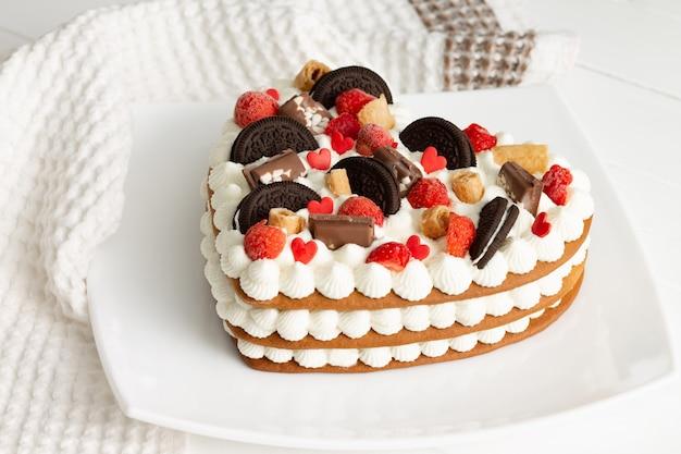 Ciasto w kształcie serca z ricottą i bitą śmietaną, ozdobione czekoladą, goframi, ciasteczkami i truskawkami