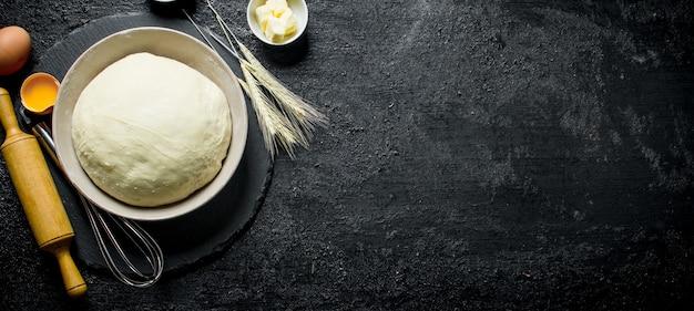 Ciasto w misce z wałkiem do ciasta, kłoskami i jajkiem na czarnym rustykalnym stole