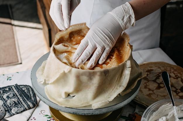 Ciasto w okrągłej patelni z kucharzem rozkładającym plastry na nim w kuchni
