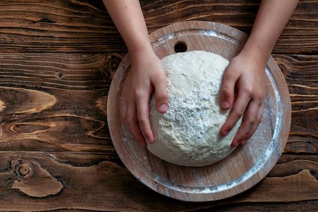 Ciasto w rękach dziecka, drewniany blat widok.