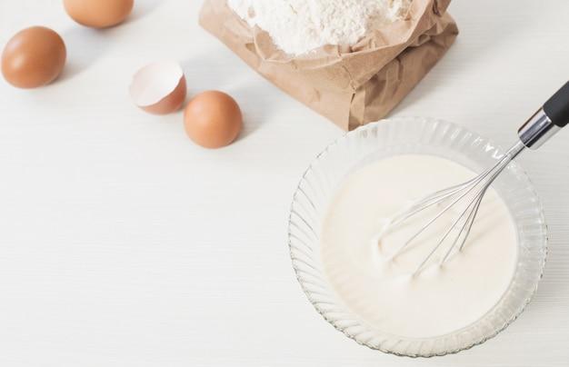 Ciasto w szklanej płytce i produkty do jego przygotowania na biało