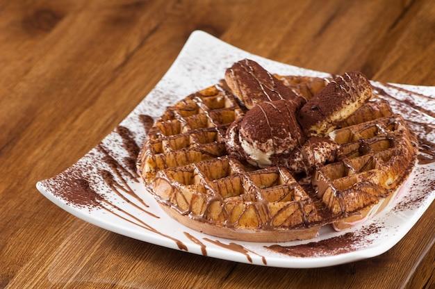 Ciasto waflowe w kwadratowym białym talerzu na drewnianej lakierowanej powierzchni z odbiciem