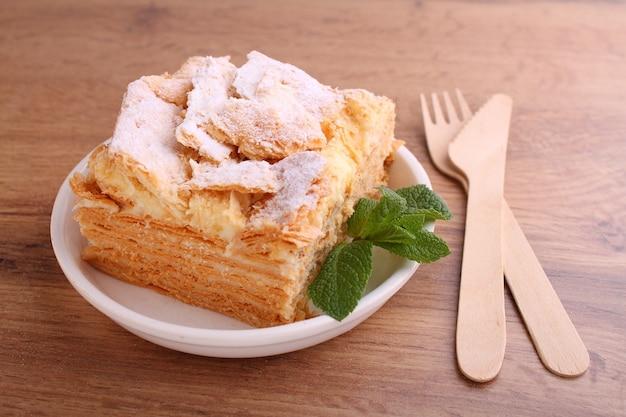 Ciasto warstwowe napoleon z plasterkiem kremu waniliowego ozdobione miętą, na talerzu na drewnianym tle.