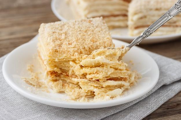 Ciasto warstwowe z kremowym plasterkiem wanilii napoleon millefeuille na białym talerzu.