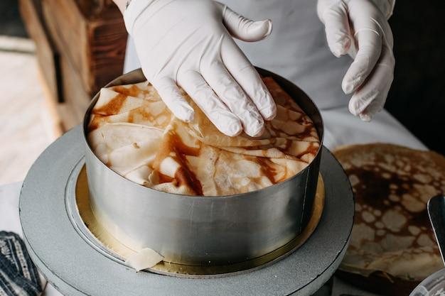 Ciasto wewnątrz okrągłej patelni z kucharzem rozkładającym plastry gotowanie posiłku na nim w kuchni