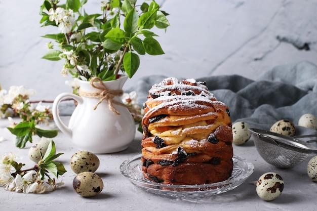 Ciasto wielkanocne craffin i jaja przepiórcze na szarym tle. koncepcja wiosennego święta kościelnego. martwa natura