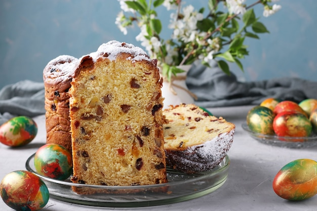 Ciasto wielkanocne craffin i marmurowe kolorowe jajka na jasnoniebieskim tle. koncepcja wiosennego święta cerkiewnego.