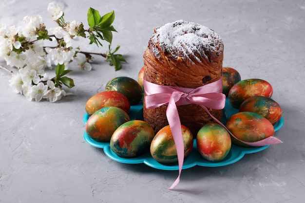 Ciasto wielkanocne craffin i marmurowe kolorowe jajka na szarym tle. koncepcja wiosennego święta cerkiewnego. format poziomy