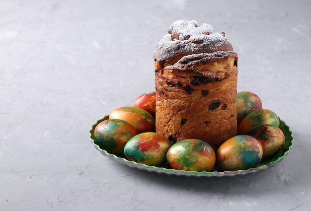Ciasto wielkanocne craffin i marmurowe kolorowe jajka na szarym tle. miejsce na tekst. koncepcja wiosennego święta cerkiewnego.