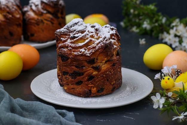 Ciasto wielkanocne cruffin i kolorowe jajka na ciemnym tle, koncepcja wiosennego święta cerkwi, orientacja pozioma, zbliżenie