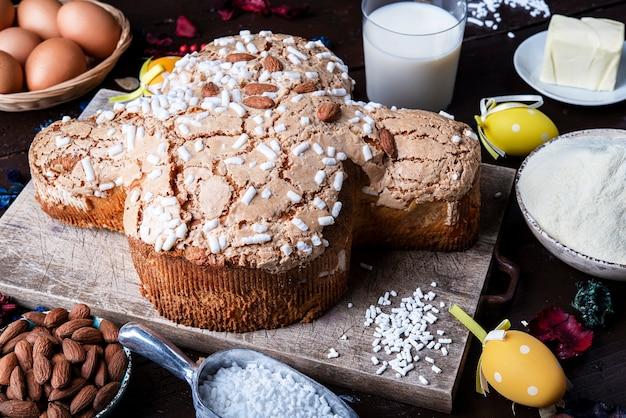 Ciasto wielkanocne dove (colomaba pasquale) tradycyjne włoskie ciasto wielkanocne na desce ze składnikami