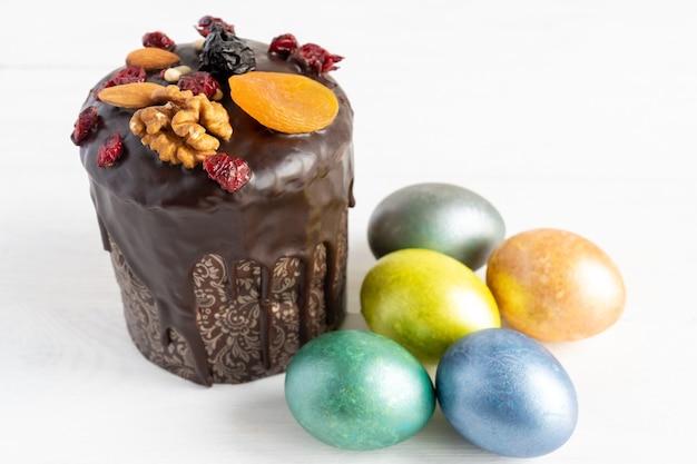 Ciasto wielkanocne i kolorowe jajka na białym tle. koncepcja jedzenie i wielkanoc wakacje.