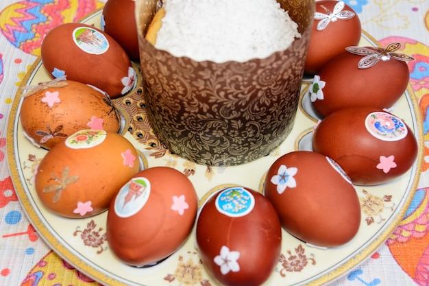 """Ciasto wielkanocne i zdobione jaja kurze ułożone na talerzu. tradycja wielkanocna: wymienia się jajka kurze i mówią: """"jezus zmartwychwstał!"""" uroczystości wielkanocne."""
