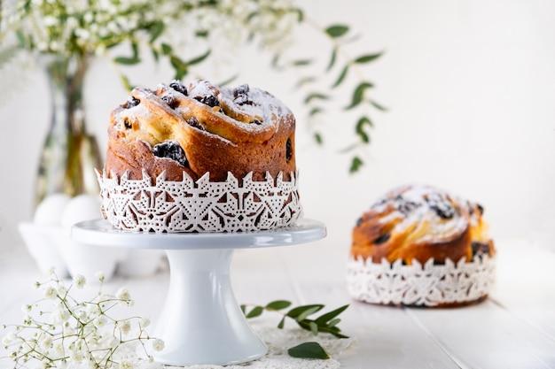 Ciasto wielkanocne kraffin. krefiny z rodzynkami, kandyzowanymi owocami i posypane cukrem pudrem. zbliżenie: domowe ciasto