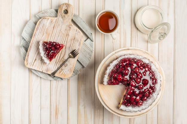 Ciasto wiśniowe z wyciętym kawałkiem na białej drewnianej desce na jasnym tle z filiżanką herbaty i cukiernicą