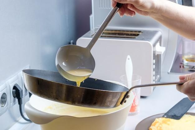 Ciasto wylewanie z metalowego wiadra na rozgrzaną do czerwoności natłuszczoną patelnię proces pieczenia naleśników