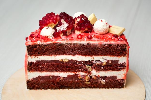 Ciasto z białą śmietaną, kroplami czekolady, granatem, orzechami i dekoracją czekoladową