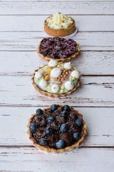 Ciasto z ciastem maślanym, polewą z kremu pistacjowego i chrupiącą perłą z białej czekolady. obok innych mini placków.