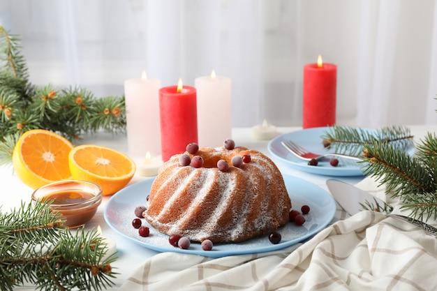 Ciasto z cukrem pudrem i żurawiną na białym stole