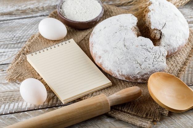 Ciasto z dużym kątem widzenia z notatnikiem, jajkami, wałkiem do ciasta na worze i drewnianą powierzchnią. poziomy