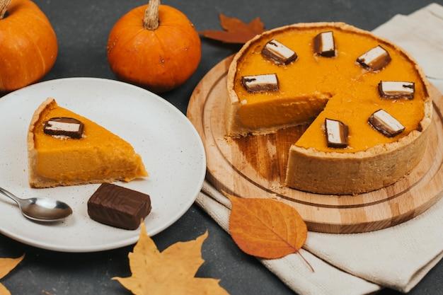 Ciasto z dyni na okrągłej drewnianej desce, kawałek ciasta na białym talerzu, jesienne liście i małe dynie.