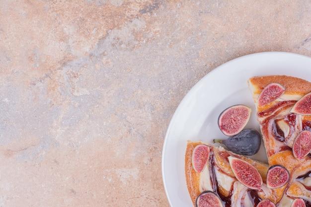 Ciasto z figami na białym talerzu na marmurze