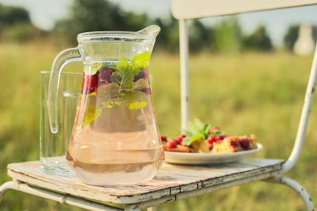 Ciasto z jagodami i dzbanek z truskawkowym napojem miętowym na słonecznej letniej łące