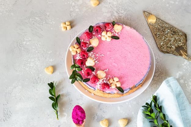 Ciasto z kremem malinowym ozdobione malinami, mini ciasteczkami i płatkami kokosowymi